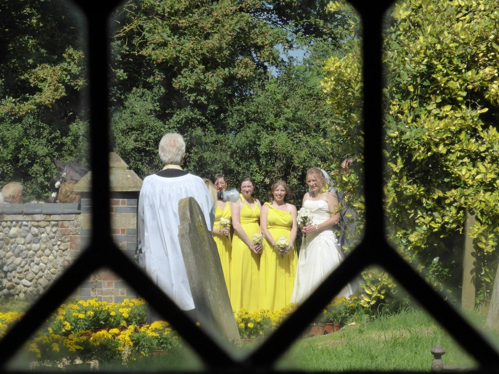 Bridesmaids through the church pane