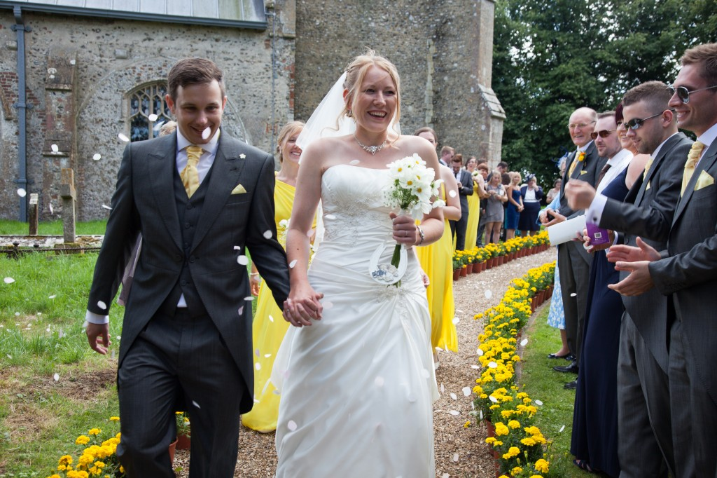 Throwing confetti at our wedding in Sharrington church