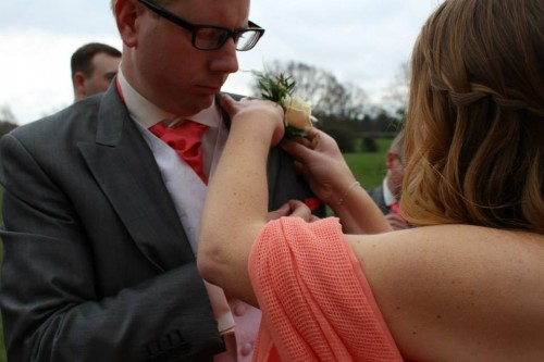 Pinning Alex's buttonhole on at their wedding