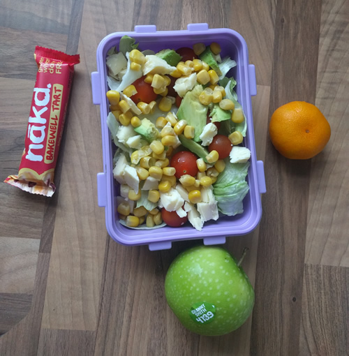 Healthy lunchbox with salad, fruit and nakd bar