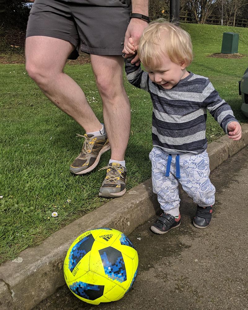 Oscar playing football in the car park